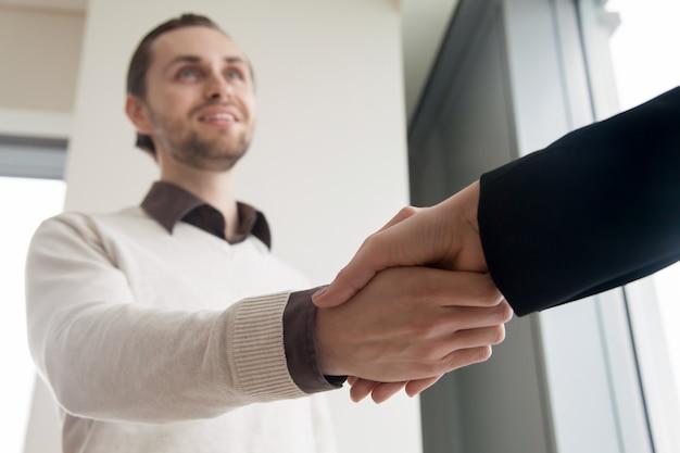 Chiuda in su della stretta di mano, dell'uomo d'affari sorridente e del cliente che agitano le mani