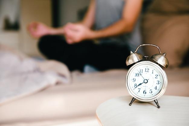 Chiuda in su della sveglia con l'uomo che fa yoga medita sul letto
