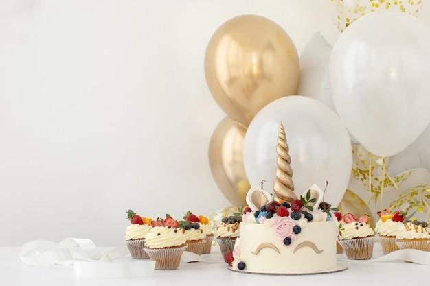 Chiuda in su della tabella della festa di compleanno della bambina con la torta dell'unicorno