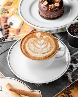 Chiuda in su della tazza del caffè del cappuccino e della torta di cioccolato