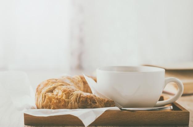 Chiuda in su della tazza di caffè con il croissant sulla tabella di legno con il tono dell'annata