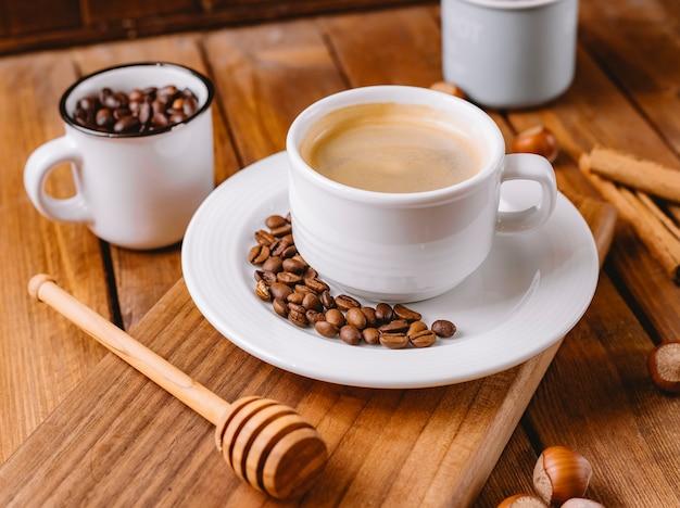 Chiuda in su della tazza di caffè decorata con chicchi di caffè disposti sul bordo di servizio in legno