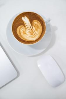 Chiuda in su della tazza di caffè di arte del latte con la disposizione del piano del computer portatile e del mouse