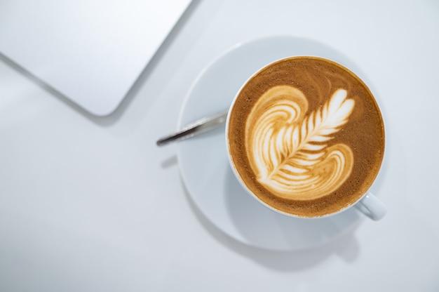 Chiuda in su della tazza di caffè di arte del latte con la disposizione del piano del computer portatile