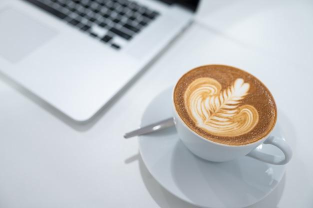 Chiuda in su della tazza di caffè di arte del latte con la tastiera del computer portatile