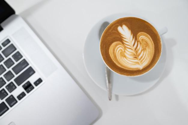 Chiuda in su della tazza di caffè di arte del latte con la tastiera della disposizione del piano del computer portatile.