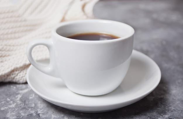 Chiuda in su della tazza di caffè e del plaid bianco del knittead sui precedenti grigi