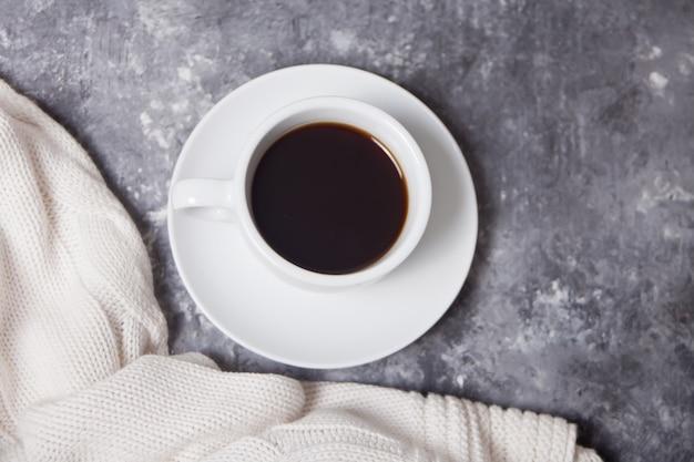 Chiuda in su della tazza di caffè e del plaid bianco del knittead sul gray