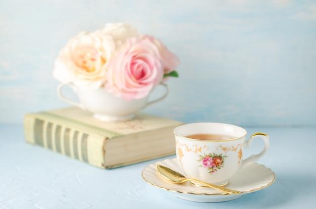 Chiuda in su della tazza di tè con i fiori e libro sull'azzurro