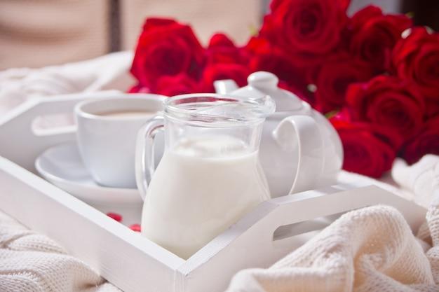 Chiuda in su della tazza di tè con le rose rosse sul vassoio bianco