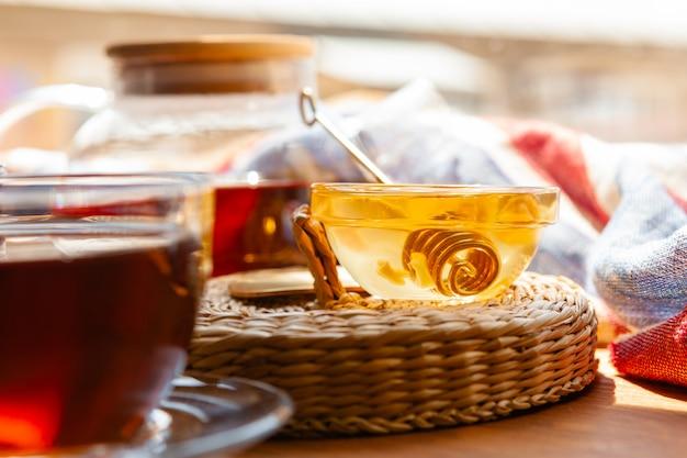 Chiuda in su della tazza di tè di vetro con miele