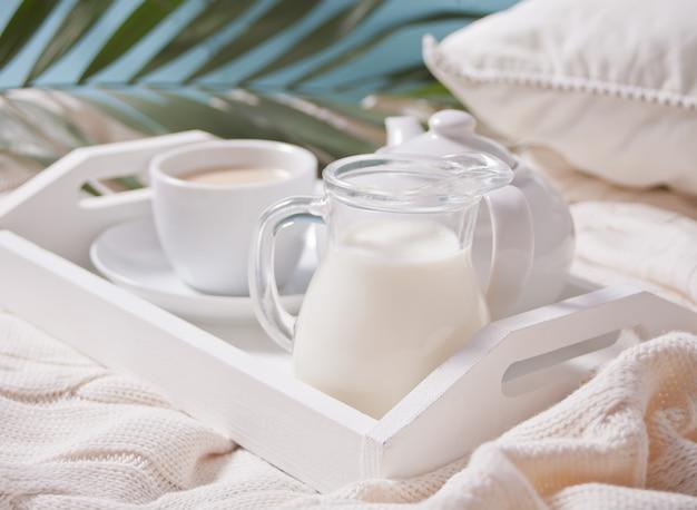 Chiuda in su della tazza di tè, latte, teiera sul vassoio bianco.