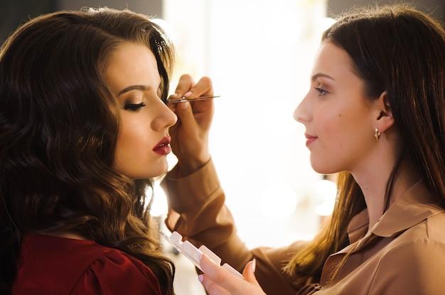 Chiuda in su delle ciglia allungamento stilista professionista per cliente femminile in un salone di bellezza