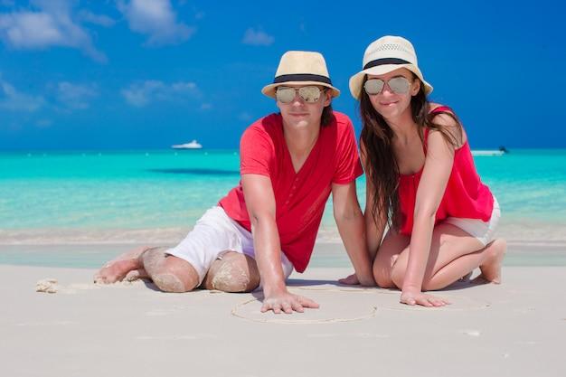 Chiuda in su delle coppie che si siedono nel cuore sulla spiaggia bianca tropicale