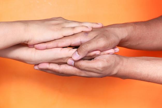 Chiuda in su delle coppie che si tengono per mano contro lo spazio arancione.