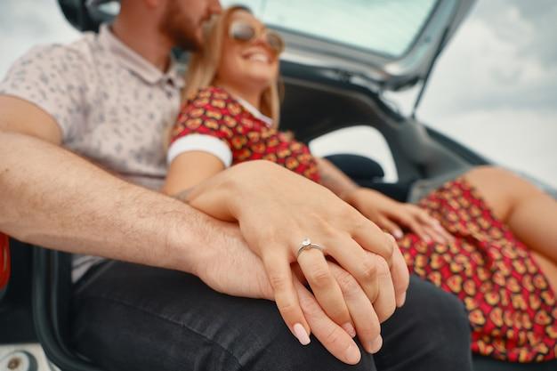 Chiuda in su delle coppie impegnate che si tengono per mano con l'anello di diamante