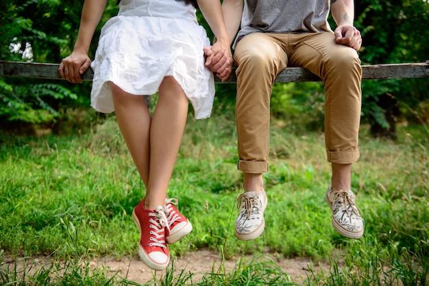Chiuda in su delle coppie nei keds che si siedono sul banco.