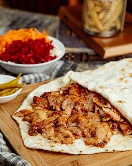 Chiuda in su delle fette del doner del pollo disposte fra flatbread