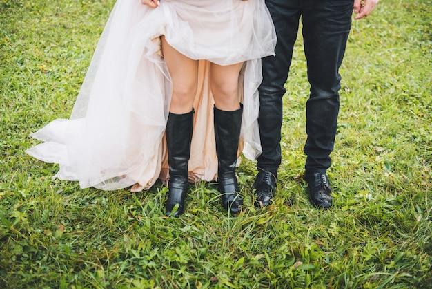 Chiuda in su delle gambe della sposa e dello sposo, levandosi in piedi vicino a vicenda su erba