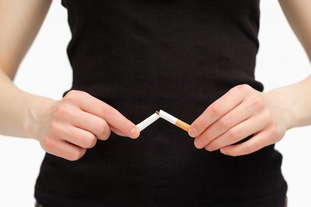 Chiuda in su delle mani che si rompono una sigaretta