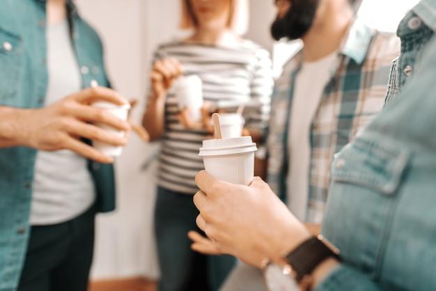 Chiuda in su delle mani che tengono il caffè per andare. avviare il concetto di business.