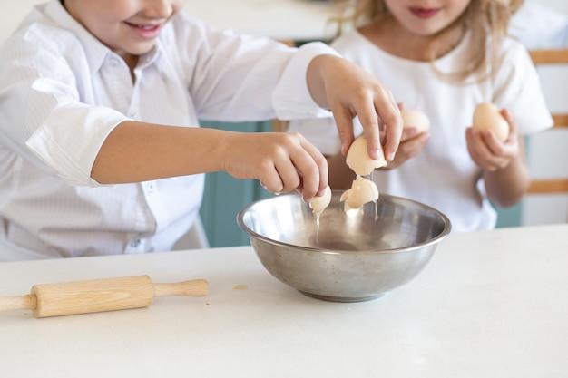 Chiuda in su delle mani dei bambini che cucinano con le uova