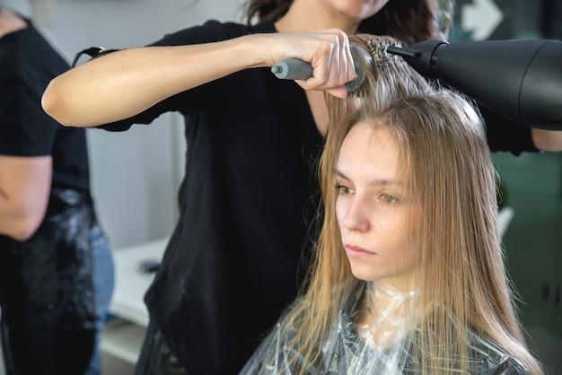 Chiuda in su delle mani dei parrucchieri che asciugano i capelli biondi lunghi con il fon e la spazzola rotonda