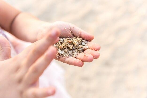 Chiuda in su delle mani del bambino che giocano con la sabbia.