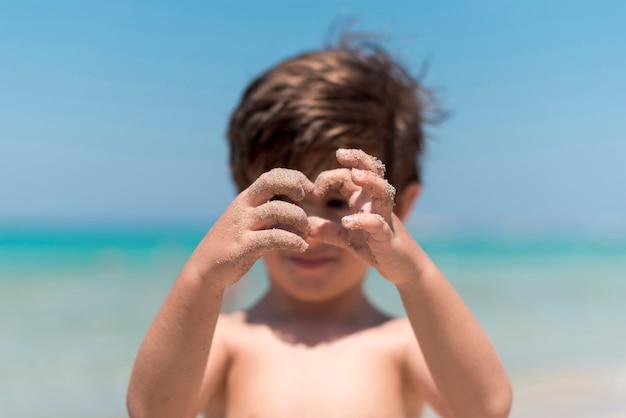 Chiuda in su delle mani del bambino che giocano in spiaggia