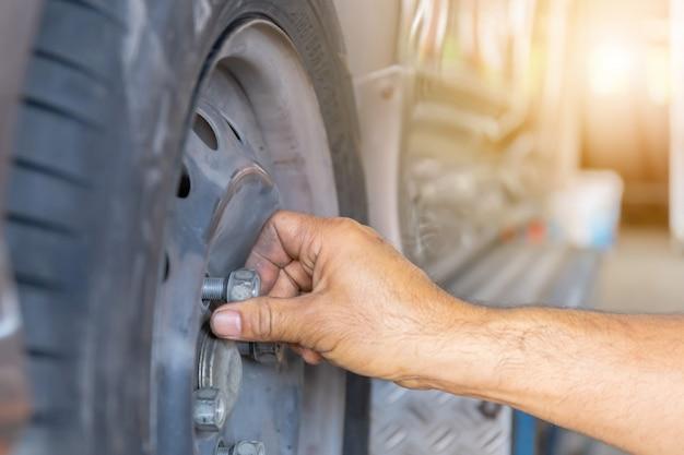Chiuda in su delle mani del meccanico di riparazione durante i lavori di manutenzione per allentare un dado della ruota che cambia pneumatico dell'automobile