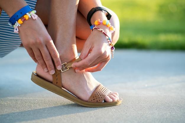 Chiuda in su delle mani della donna che legano le sue scarpe dei sandali.