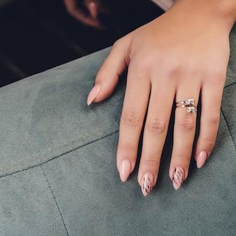 Chiuda in su delle mani della donna che mostrano l'anello con il diamante. è fidanzata.
