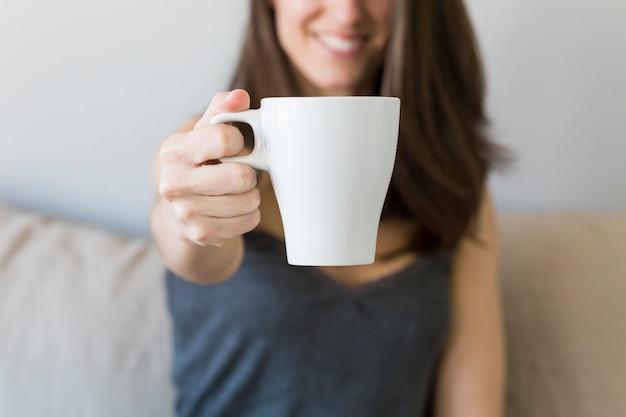 Chiuda in su delle mani della donna che tengono una tazza di caffè nella sua camera da letto