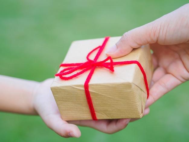 Chiuda in su delle mani della madre e del bambino con il contenitore di regalo sopra priorità bassa verde