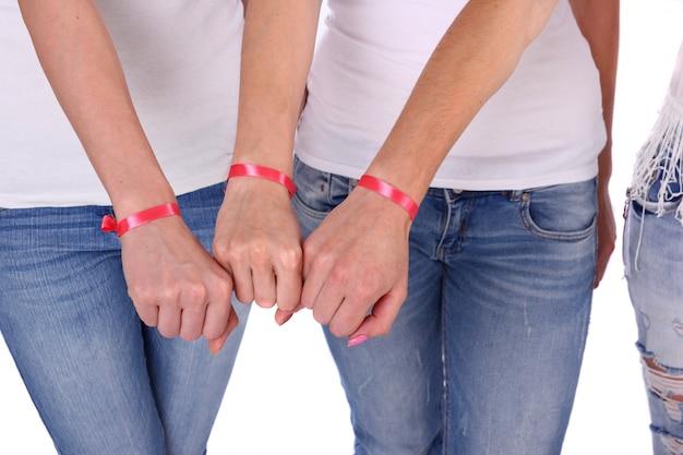 Chiuda in su delle mani delle donne con nastri di consapevolezza del cancro