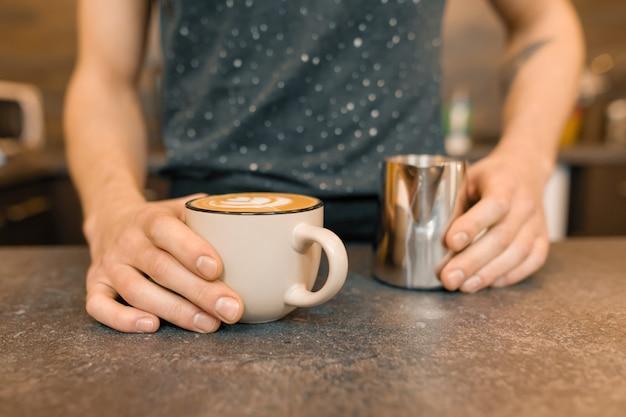 Chiuda in su delle mani di baristi e caffè appena preparato di arte con schiuma e reticolo