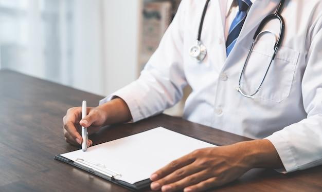 Chiuda in su delle mani di seduta del medico al tavolo e scrivere una prescrizione, assistenza sanitaria e medica.