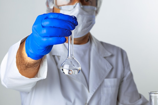 Chiuda in su delle mani di uno scienziato che lavora con campioni di laboratorio