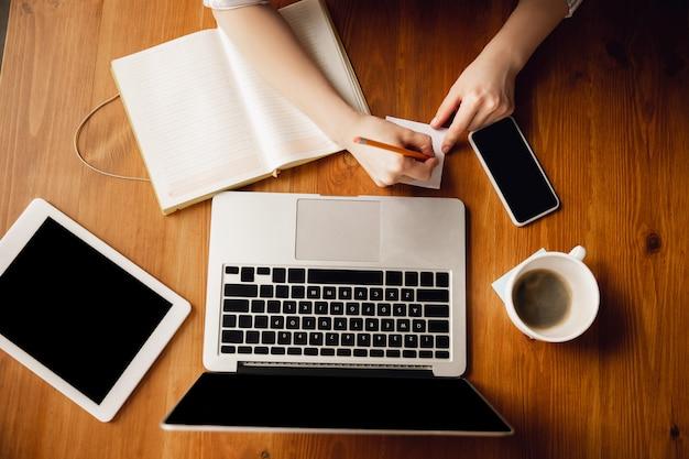 Chiuda in su delle mani femminili caucasiche durante il lavoro in ufficio, studiando, vista dall'alto