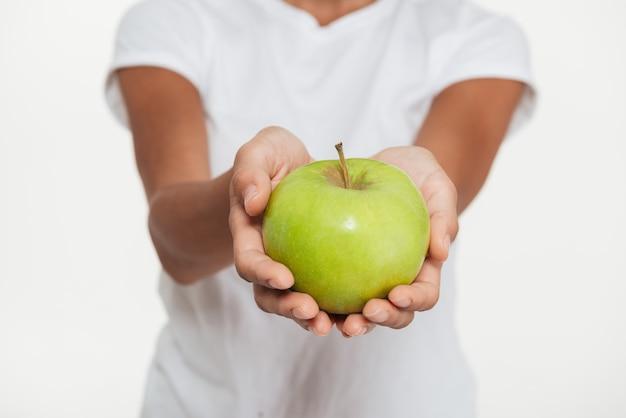 Chiuda in su delle mani femminili che mostrano la mela verde