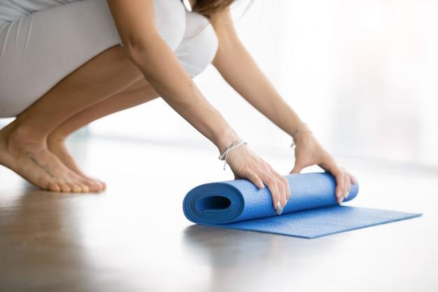 Chiuda in su delle mani femminili che si svolgono i materassi di yoga