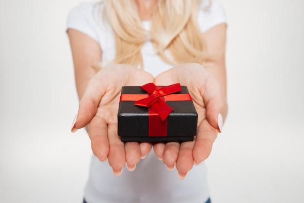 Chiuda in su delle mani femminili che tengono poco contenitore di regalo