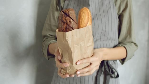 Chiuda in su delle mani femminili di un fornaio o di un venditore in uniforme con gustose baguette su uno sfondo grigio