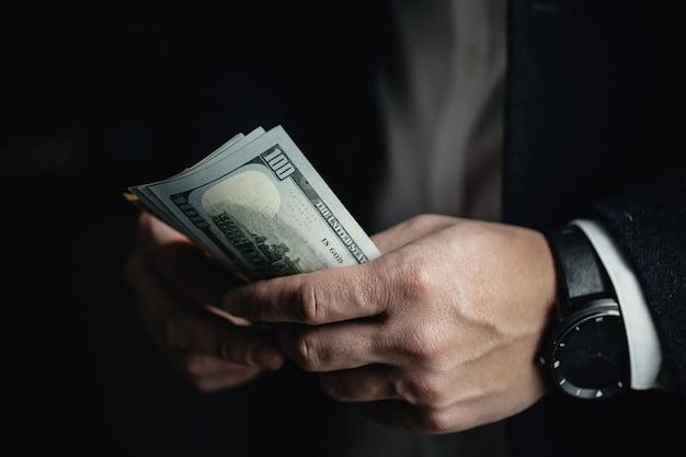 Chiuda in su delle mani maschii che contano le banconote in dollari