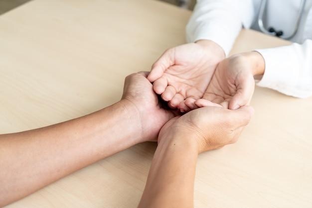 Chiuda in su delle mani vuote che tengono nella casa di cura