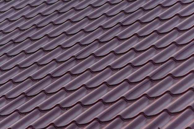 Chiuda in su delle mattonelle di tetto di plastica rosse per priorità bassa