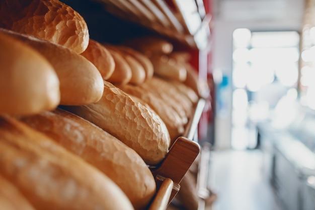 Chiuda in su delle pagnotte di pane deliziose fresche nella riga sugli scaffali pronti per la vendita. interno di panetteria.