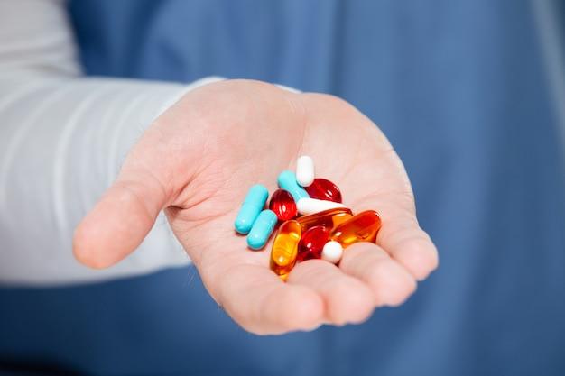 Chiuda in su delle pillole maschii della holding della mano del medico