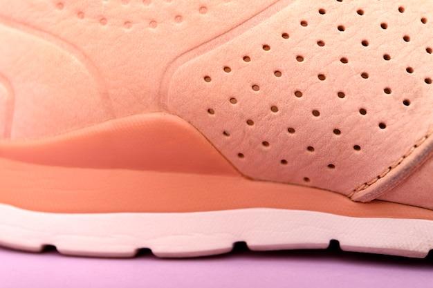 Chiuda in su delle scarpe da tennis alla moda sul colore rosa