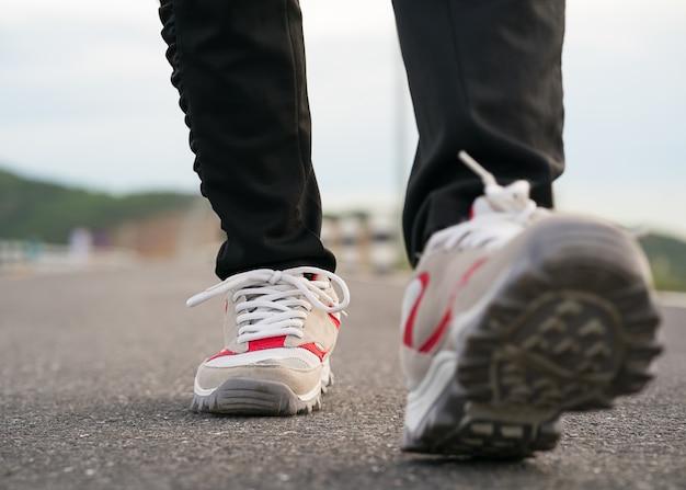 Chiuda in su delle scarpe della ragazza che camminano